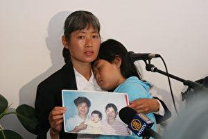 """Der Schmerz bleibt: Frau Zhizhen Dai, Diskussionsteilnehmerin beim Forum """"Nie wieder! - Aufruf an die Welt"""", bei dem der Organraub in den Todeslagern in China diskutiert wurde, spricht von der Folter und dem Mord an ihrem Ehemann im Jahre 2001 durch die Hand chinesischer Behörden. Ihre Tochter Fadu schläft in ihren Armen. Das Forum wurde am 9. Mai 2006 in Auschwitz in Polen gehalten. (Jan Jekielek/The Epoche Times)"""
