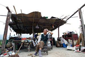DACHANG STADT, 3. JUNI: Ein älterer Bürger sitzt neben seiner Wohnung, ein aus den Ruinen der zerstörten Häuser erbauter Unterstand. Dachang war eine etwa 1,700 Jahre alte Stadt. Die Gebäude werden abgerissen und auf ein Gelände ungefähr 7 Kilometer von der Altstadt entfernt wieder aufgebaut. (