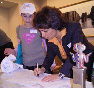 Sarah Marie möchte ihr Switch-Shirt in einer anderen Größe, Frau Pourkian kümmert sich darum. Im Vordergrund: die Goldene Göre, der Preis vom Deutschen Kinderhilfswerk (