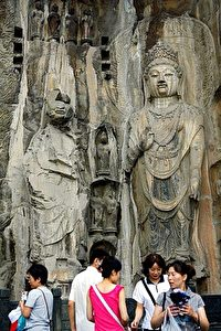 Tourists visit the Longmen Grottoes Buddhist sculptures. Damage to the face of the left-hand statue is clearly visible. (Teh Eng Koon/AFP/Getty Images)