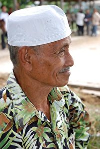 PROUD ONLOOKER: Mr. Alin, owner of the sure-footed Kompang Jaya, watches the buffalo races. (Wes Lafortune)