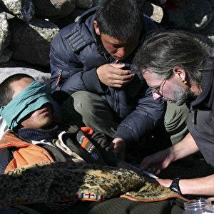 Auf 4300 Meter Höhe wird ein provisorisches Krankenlager eingerichtet und die Erfrierungen werden aufgetaut. Wegen ihrer Schneeblindheit bekommen die Jugendlichen ein Tuch vor ihre Augen gebunden. (Christian Gatniejewski)