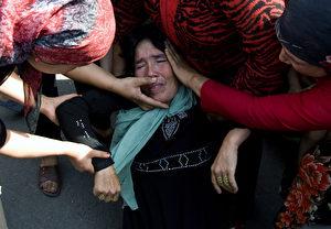 Eine Uigurin, die am Dienstag beim Protest gegen die Gefangennahme der Männer zusammenbrach. Das Foto wurde aufgenommen, als noch Journalisten in der Stadt sein durften.  (AP Photo/Ng Han Guan)
