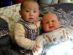 Kleinkind mit chinesischer Puppe, 2009 von Kelsang Tsering (geb. 1969). Traditionell gibt es in Tibet keine speziellen Spielsachen und Puppen für Kinder. Die Babypuppe aus Plastik stammt aus China und wurde wohl ursprünglich für den westlichen Markt hergestellt. (Kelsang Tsering)