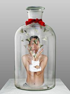 Mann in Flasche, 2009. Eine Fotomontage: Der in der Flasche gefangene Künstler Nortse (geb. 1963) wirft mit gebundenen Armen Schmetterlinge mit tibetischer Schrift in die Luft! Um den Flaschenhals ist ein rotes Tuch geschlungen. Anspielung auf das rote Tuch der jungen Pioniere, Jugendorganisation der KP? (Nortse)
