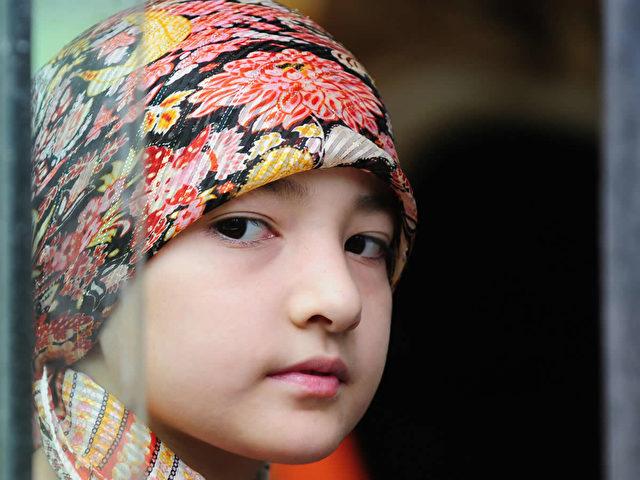 Ein junges uigurisches Mädchen schaut in Urumqi, in der Provinz Xinjiang aus einem Busfenster.  (Frederic J. Brown/AFP/Getty Images)
