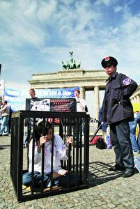 Archivbild - Eine Szene der Verfolgung und Folter wird dargestellt, der Praktizierende der spirituellen Bewegung Falun Gong durch das chinesische kommunistische Regime unterworfen sind. Diese außergewöhnliche Demonstration fand vor dem Brandenburger Tor in Berlin statt.