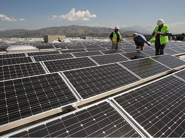Arbeiter installieren Solarmodule auf dem Dach des Sam's Club-Kaufhauses in Glendora, Kalifornien. Foto: David McNew/Getty Images
