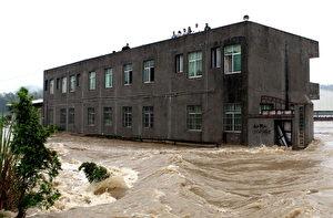 Mehrere Personen sitzen am 6. Juni auf einem Fabrikgebäude fest und warten darauf, gerettet zu werden. Starkes Hochwasser hat das Gebäude in Jiujiang, in der chinesischen Provinz Jiangxi, umgeben.