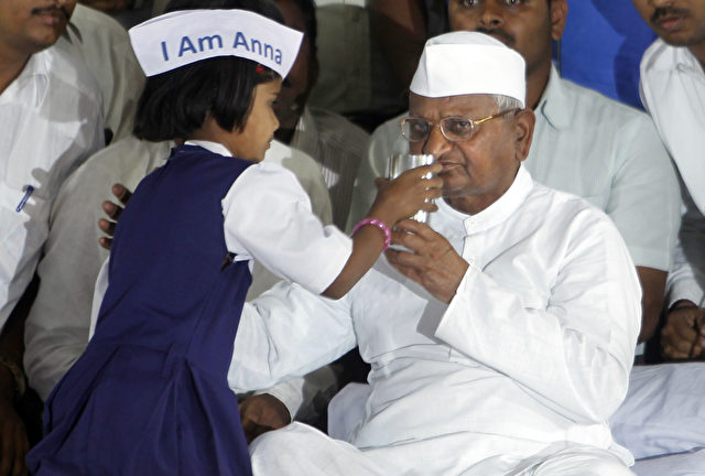 Anti-Korruption-Aktivist Anna Hazare bekommt von einem kleinen Mädchen ein Glas Saft gereicht, womit er seinen Hungerstreik beendete. Foto: AP Photo/Rafiq Maqbool
