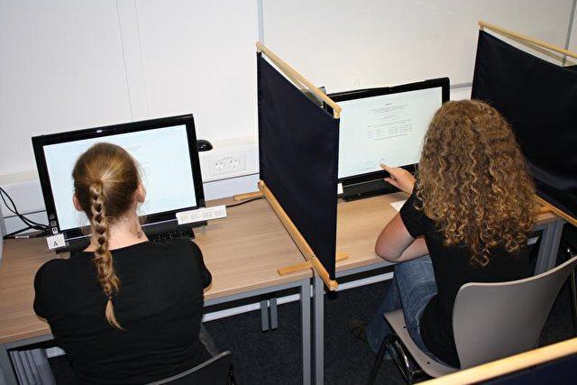 Studierende spielen anonym und durch einen Sichtschutz getrennt am Computer die kooperativen Spiele. Foto: Universität Göttingen