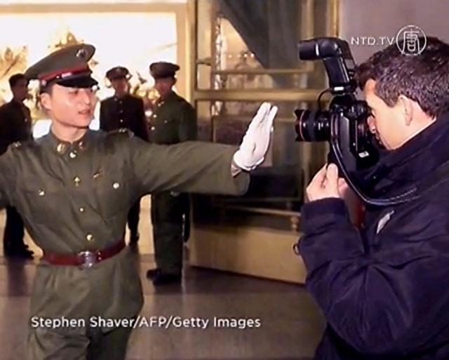 Chinesischer Polizist stoppt einen Journalisten.   Foto: Stephen Shaver/AFP/Getty Images