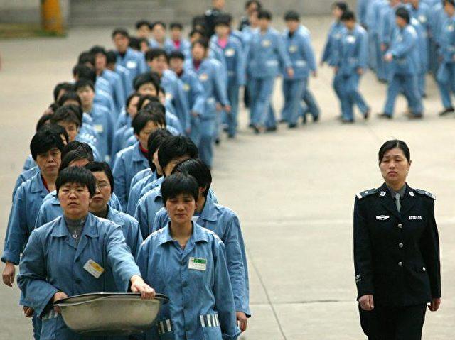 """Gefangene neben einer Wärterin bei einem """"Tag des offenen Gefängnisses"""" in Nanjing 2005.   Foto: STR/AFP/Getty Images"""