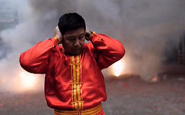 Chinesischer Bürger während des Feuerwerks zum chinesischen Neujahr.   Foto: NTD Television