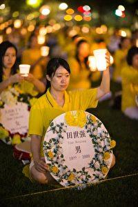 Falun Gong-Praktizierende gedenken der Toten, die die Verfolgung in China gefordert hat. Im Hintergrund sitzen Hunderte in Reihen in vollkommener Stille.