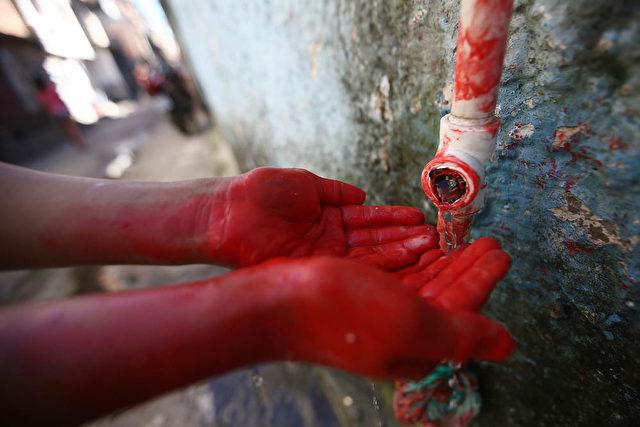 Ein Demonstrant in Sao Paulo wäscht sich nach einem Anti-WM-Protest am 14. Juni rote Farbe von den Händen, welche das Blut der ermordeten Einwohner seiner Favela darstellen sollte. Foto: Mario Tama / Getty Images