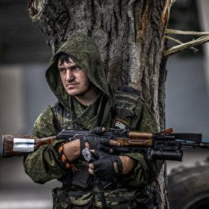 Ein pro-russischer Separatist geht an einem Kontrollpunkt am nördlichen Stadtrand von Stadt Donezk mit seiner Waffe hinter einem Baum in Deckung. Foto: BULENT KILIC / AFP / Getty Images
