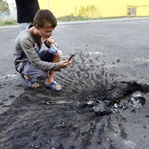 Ein kleiner Junge macht eine Foto von einem Krater im Asphalt, in der östlichen ukrainischen Stadt Donetsk, am 22. Juli. Foto: Alexander KHUDOTEPLY / AFP / Getty Images