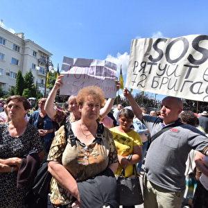 """Verwandte von ukrainischen Bediensteten, die gegen pro-russische Militärs im Osten der Ukraine kämpfen, halten Plakate mit der Aufschrift """"SOS! Foto: SERGEI SUPINSKY / AFP / Getty Images"""