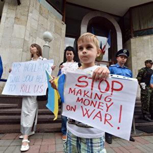 Ein Junge hält ein Schild während einer Demonstration vor der französischen Botschaft in Kiew, am 22. Juli 2014, um gegen den Verkauf von Kriegsschiffen der Mistral-Klasse an Russland zu protestieren. Foto: SERGEI SUPINSKY / AFP / Getty Images