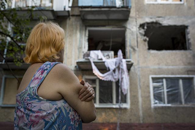 Eine Anwohnerin schaut auf ein durch Raketenbeschuss zerstörtes Gebäude in Donetsk, am 22. Juli 2014.  Foto: Rob Stothard/Getty Images