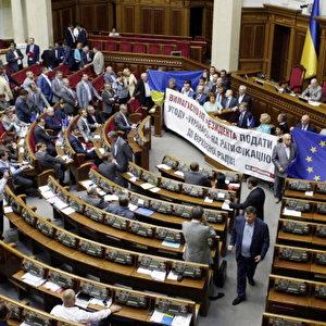"""Die Abgeordneten der Batkivshchyna oder All-Ukrainischen """"Vaterland""""-Union halten eine Fahne der Europäische Union (EU), eine ukrainische Fahne und ein Transparent mit der Aufschrift """"Aufforderung an den Präsidenten dem Parlament eine Ratifizierung des Vertrags zwischen der EU und der Ukraine zu unterbreiten!"""" Foto: Anatolij Stepanov / AFP / Getty Images"""