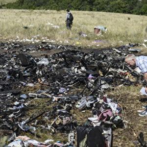 Ein Mann schaut auf Trümmer an der Stelle des abgestürzten Malaysia Airlines Fluges MH17, die verstreut auf Feldern in der Nähe des Dorfes Grabove, Donezk, liegen. Foto: BULENT KILIC / AFP / Getty Images