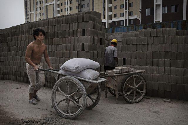 Ein chinesischer Bauarbeiter auf der Baustelle eines neuen Apartment-Komplexes in Peking.     Foto: Kevin Frayer / Getty Images