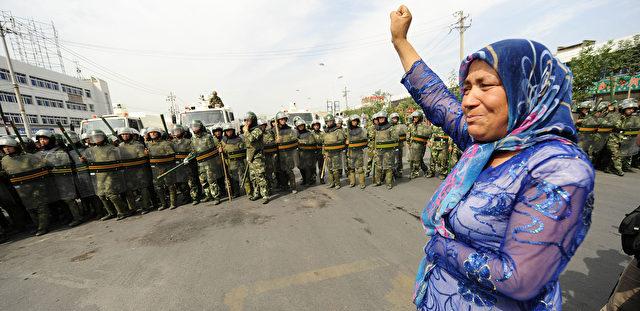 Eine uigurische Frau steht einer Gruppe chinesischer Polizisten gegenüber Foto: PETER PARKS/Getty Images