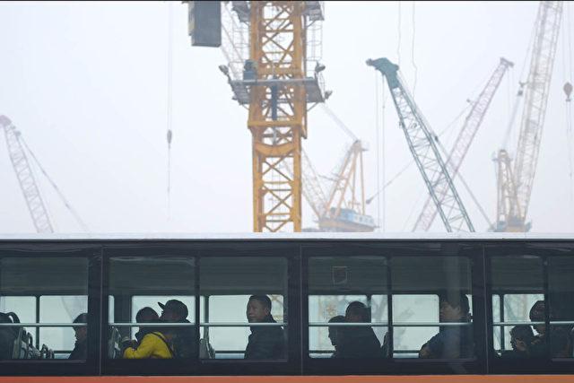 Ein Bus fährt an einer Pekinger Großbaustelle vorbei (20. November 2014). Foto: WANG ZHAO/AFP/Getty Images