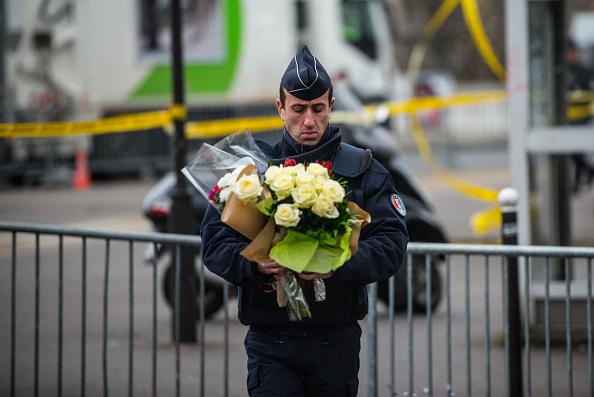 PARIS, FRANKREICH - 10. Jänner: Ein Polizist trägt die Kondolenz-Blumen eines Passanten zum Ort des Attentats. Foto: David Ramos/Getty Images