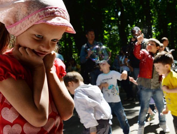 Ein Mädchen blickt anteilslos, während andere Kinder mit  Seifenblasen spielen. Foto: AFP / Getty