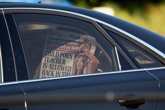 """Ein Teilnehmer der Bilderber-Konferenz am 6. Juni 2013 in Watford, England verdeckt sein Gesicht bei der Ankunft im The Grove Hotel mit einer Ausgabe der """"Daily Mail"""". Foto: Oli Scarff/Getty Images"""