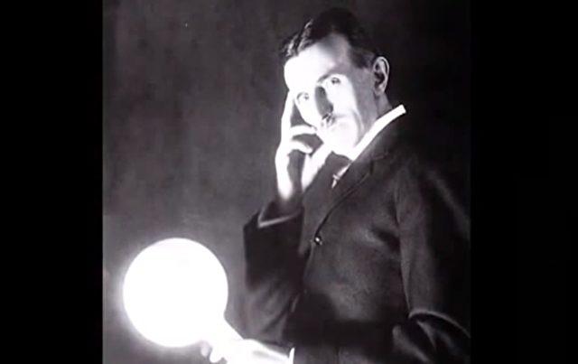 : Tesla mit Glühbirne, Tesla fungiert hier anscheinend als Erde, während die Fassung-Glühdraht-Konfiguration teilweise oder insgesamt als Empfänger dient.