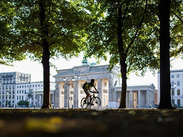 Radeln vor historischer Kulisse: Vor dem Brandenburger Tor führt der Weg in Berlin in den Tiergarten hinein. Foto: Lukas Schulze/dpa