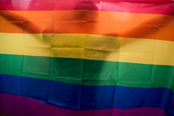 Ein Mann hält eine Regenbogenfahne. Foto: Getty Images