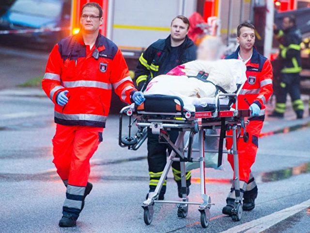 In Hamburg-Bahrenfeld bringen Feuerwehrleute eine Frau zu einem Rettungswagen. Foto: Daniel Bockwoldt/dpa