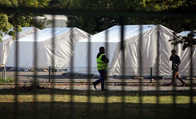"""Flüchtling und Sicherheitsmann in einer """"Zeltstadt"""" Foto: über dts Nachrichtenagentur"""