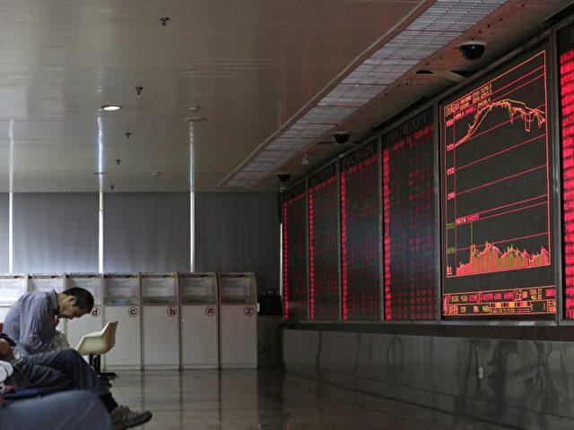 Erschöpft und enttäuscht wirkt dieser Mann, der in Peking die neuesten Zahlen vom Aktienmarkt verfolgt. Foto: How Hwee Young/dpa
