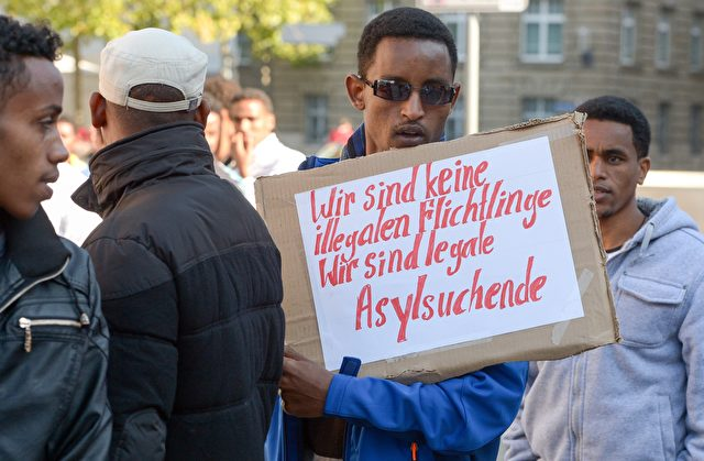 """Ein Flüchtling aus Eritrea hält ein Plakat zu lesen: """"Wir sind keine illegalen Flüchtlinge - Wir sind legale Asylbewerber"""", während einer Demonstration gegen das deutsche Verfahren für die Gewährung des Asylrechts am 2. Oktober 2015 in Erfurt, östlichen Deutschland. Foto: AFP / Getty Images"""