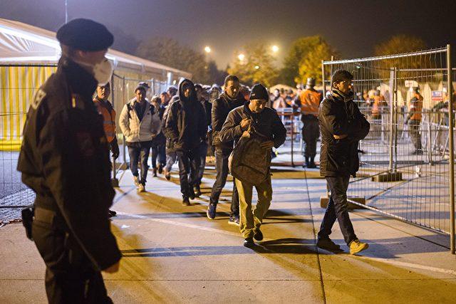 Migranten warten auf einen Bus, bevor sie in das österreichische Flüchtlingszentrum am 17. Oktober 2015 auf der österreichischen Seite des Grenzübergangs zwischen Sentilj (Slowenien) und Spielfeld gebracht werden. AFP PHOTO / Jure Makovec (Photo credit should Jure Makovec Lese- / AFP / Getty Images)