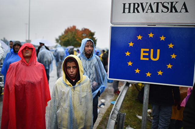 Migranten warten im Regen am Trnovec Grenzübergang nach Slowenien am 19. Oktober 2015. Slowenisch Behörden haben die Grenze geschlossen nachdem das tägliche Kontingent erreicht wurde. Foto: Jeff J Mitchell / Getty Images