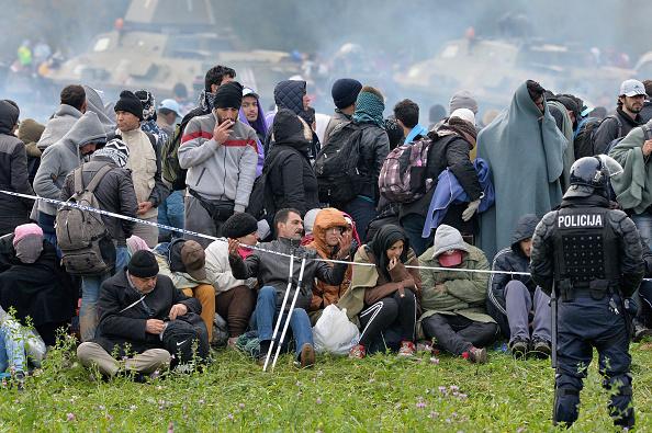 Nachdem Migranten die Grenze von Kroatien nach Slovenien überquerten, werden sie von der Polizei nahe dem Dorf Dobova, Slovenien, zurückgehalten, bevor sie zur Notunterkunft begleitet werden. Foto: Jeff J Mitchell / Getty Images
