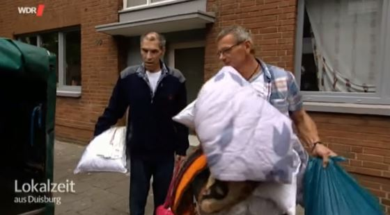 Raimund (L) und Anton Gacionis laden die Habseligkeiten vom Zwischenlager in einen Autoanhänger Foto: Screenshot/youtube