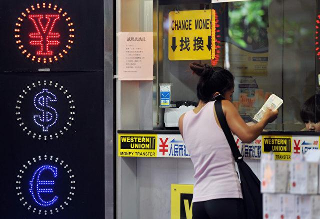 Geldwechsel vor einem entsprechenden Laden in Hongkong. Der größte bisher bekannte Ring von illegalen Geldwechslern ist aufgeflogen, es geht um 410 Milliarden Yuan, das entspricht ca. 60 Milliarden Euro. Foto: LAURENT FIEVET/AFP/Getty Images