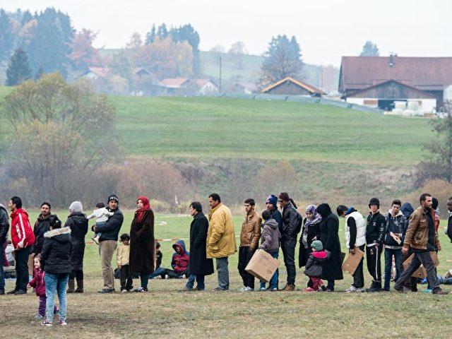 Migranten warten bei Hanging an der deutsch-österreichischen Grenze auf ihre Einreise nach Deutschland. Foto: Armin Weigel/dpa