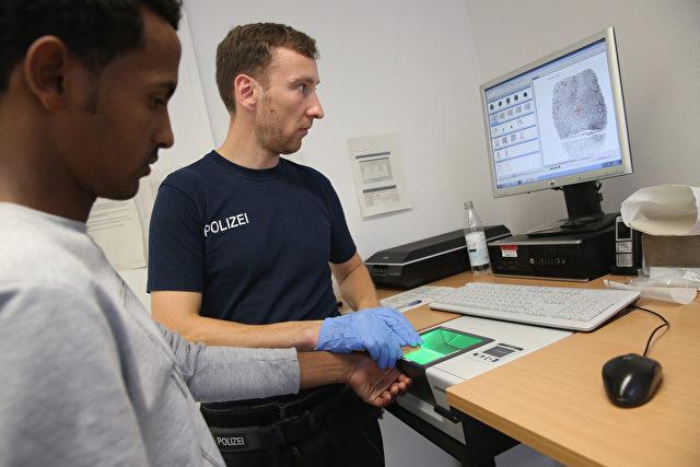Bundespolizist beim Abnehmen der Fingerabdrücke, Rosenheim Foto: Sean Gallup/Getty Images, August 2015