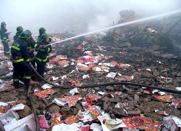 Feuerwehrmänner versuchen die Brandherde nach einer in einer Feuerwerksfabrik in China zu löschen. Bei der Explosion in 2005 kamen 25 Menschen ums Leben. Foto: China Photos/Getty Images