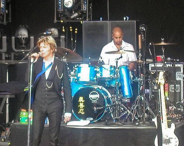 David Bowie und sein Schlagzeuger Sterling Campbell. Auf dem Schlagzeug stehen die chinesischen Schriftzeichen Zhen, Shan, Ren - Prinzipien des Falun Dafa. Foto: Facebook/Screenshot