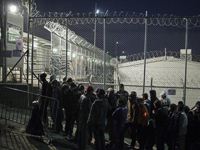 Eine Gruppe von Männern wartet auf der griechischen Insel Lesbos auf die Registrierung durch die Behörden. Foto: Socrates Baltagiannis/dpa